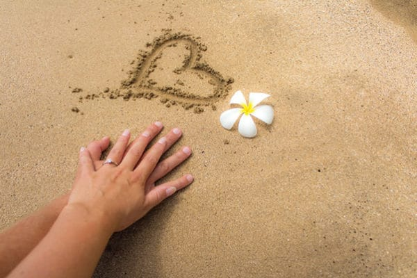 sand with heart, flower and holding hands