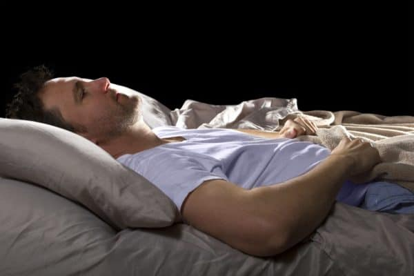Man lying in bed can't sleep