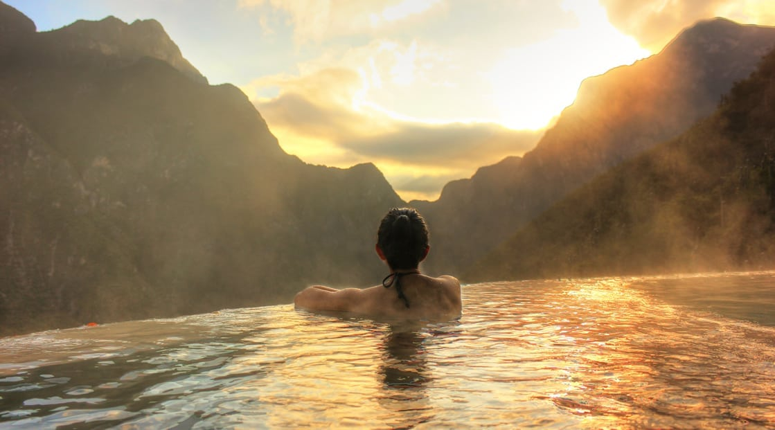 woman in pool overlooking mountains at sunset