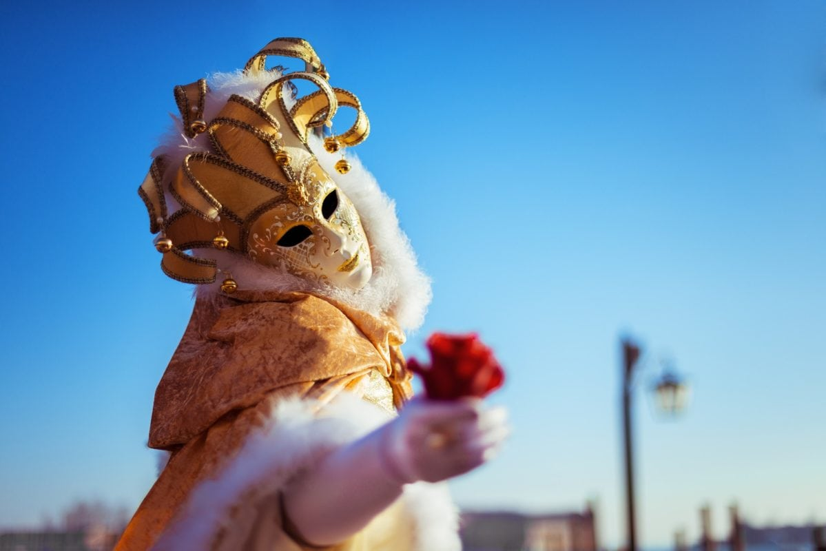 masked person holding a rose